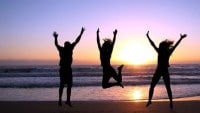 3_people_jumping_beach_sunset