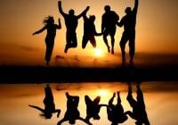 silhouette of friends jumping on beach in sunset